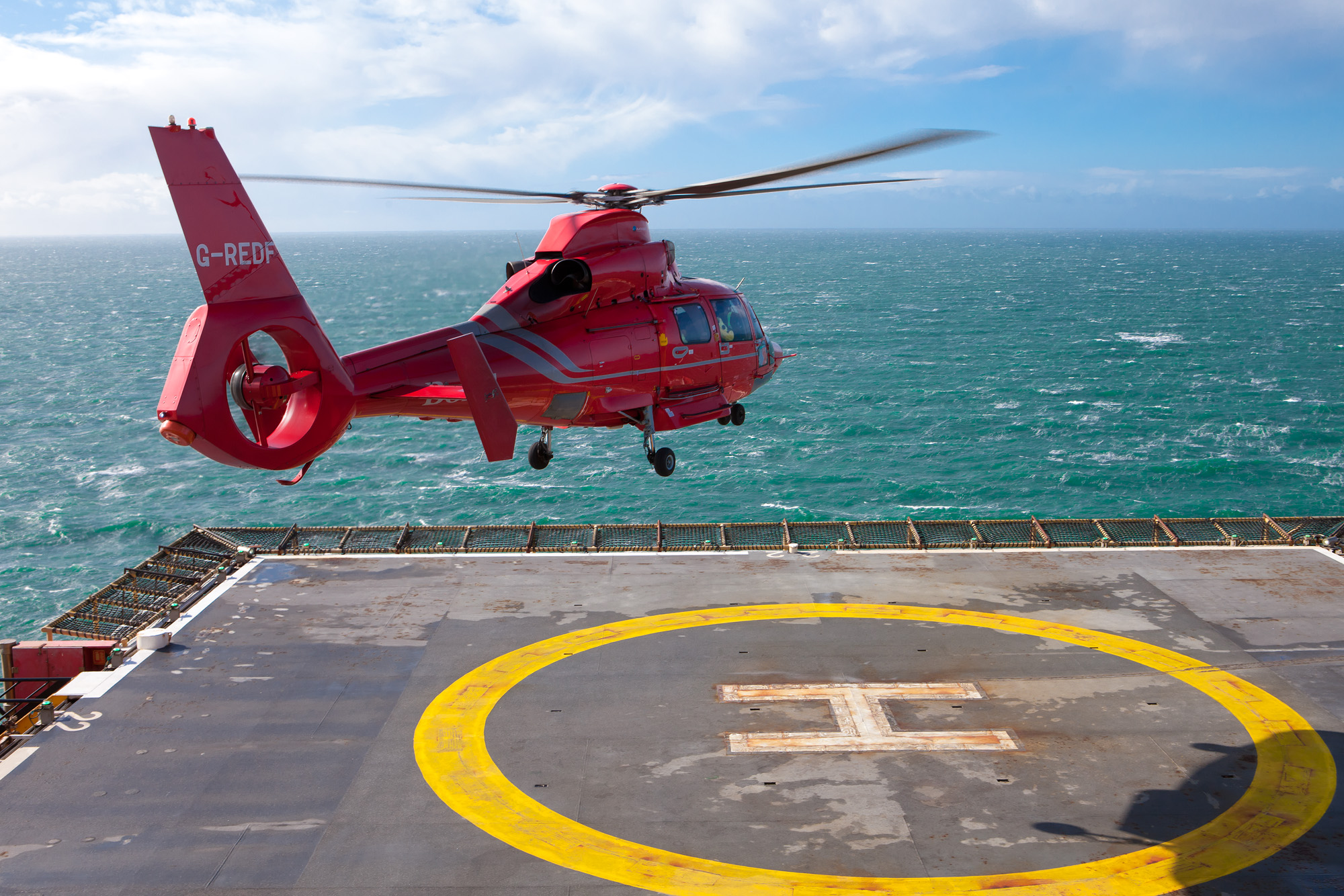 Aerospatiale AS365 Dauphin II helicopter landing on a gas rig helipad, Irish Sea