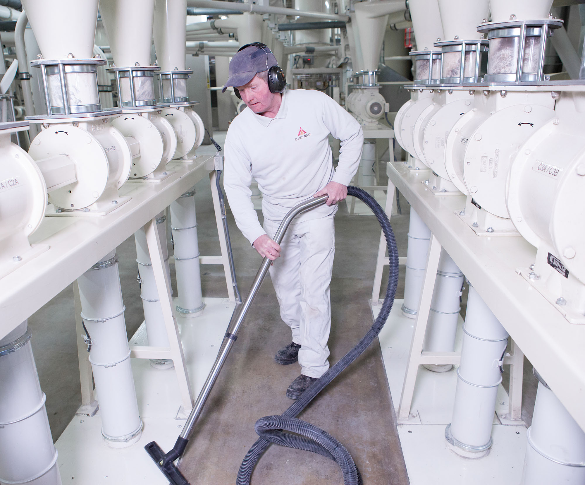 Kingsmill/Allied Bakeries Mill worker using a vacum cleaner